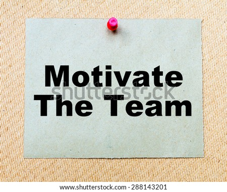 Motivate The Team written on paper note pinned with red thumbtack on wooden board. Business conceptual Image - stock photo