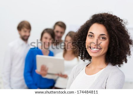 Motivated African American businesswoman with a curly afro hairstyle and beautiful beaming smile posing in the foreground while her colleagues work behind - stock photo