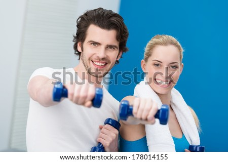 Motivated attractive young couple working out with dumbbells standing side by side giving the camera a friendly smile - stock photo