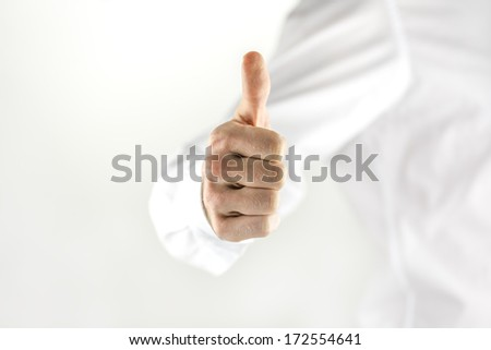 Motivated man giving a thumbs up sign showing his approval or success, high key image with copyspace and focus to his hand - stock photo