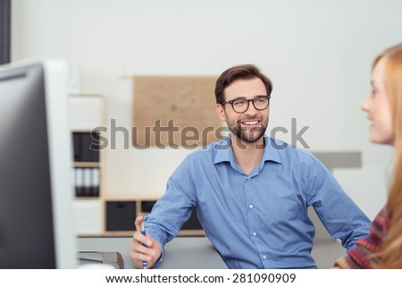 Motivated smiling businessman wearing glasses discussing a project with a female colleague in the office - stock photo