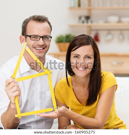 Motivated young couple planning for a home sitting close together holding up a builders reticulated ruler formed into the outline of a house - stock photo