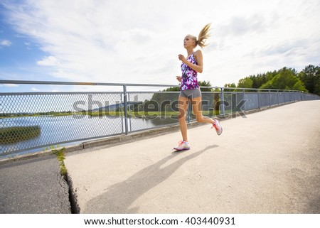 Motivated young woman running fast on bridge over a lake - stock photo