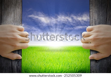 Motivation concept. Hand opening an old wooden door and found a texts floating over green field and bright blue Sky Sunrise. - stock photo