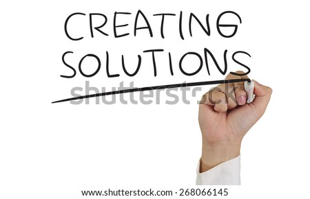 Motivational concept image of a hand holding marker and write Creating Solutions isolated on white - stock photo