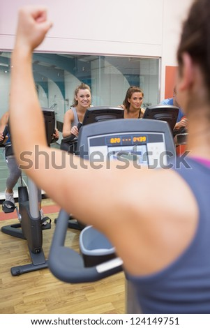 Motivational female instructor teaches spinning class at gym - stock photo