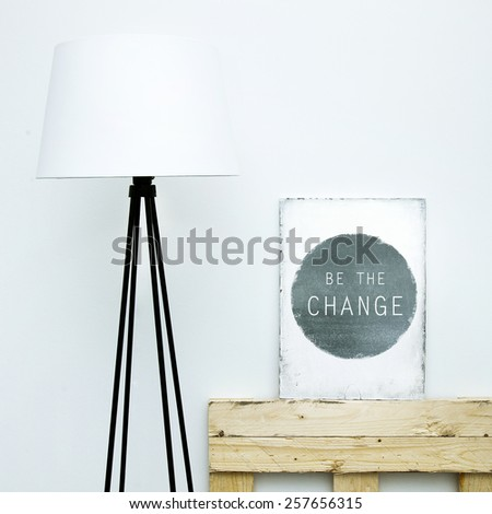 Motivational hipster board BE THE CHANGE with lamp. Scandinavian  style room interior - stock photo