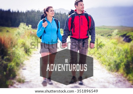 Motivational new years message against hikers with backpacks holding hands and walking - stock photo
