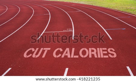 Motivational quote written on running track: Cut Calories - stock photo