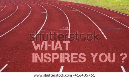 Motivational quote written on running track : What Inspires You? - stock photo