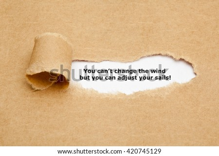 Motivational quote You can not change the wind but you can adjust your sails, appearing behind torn paper. - stock photo
