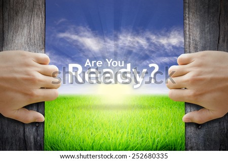 "Motivational quotes ""Are you Ready"" . Hands opening a wooden door then found a texts floating among new world as green grass field, Blue sky and the Sunrise. - stock photo"