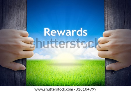 "Motivational quotes ""Rewards"". Hands opening a wooden door then found a texts floating among new world as green grass field, Blue sky and the Sunrise. - stock photo"