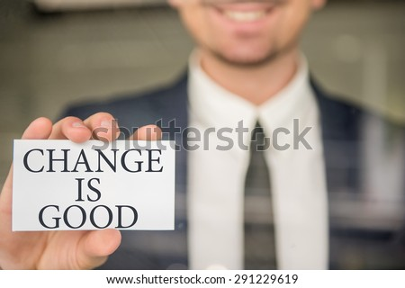 Motivational slogan written on a card in businessman's hand. - stock photo