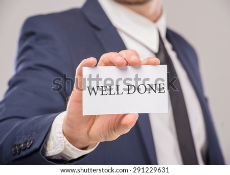 Motivational slogan written on a card in businessman's hand. - stock photo