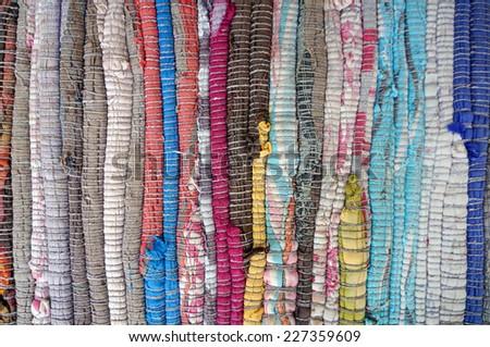 Motley rug textile fabrics texture - stock photo