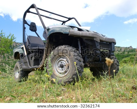 Moto all-terrain vehicle in mountains against blue sky - stock photo