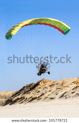 Moto paraglider on the beach - stock photo