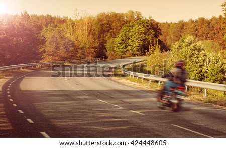Motobike on asphalt road in beautiful summer evening at countryside - stock photo
