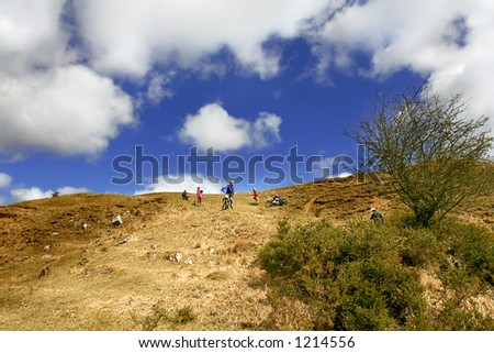 Motocross Background. Nice detail on a wide angle Lens as Biker comes down worn path on a blustery bright day in Northumberland, England. - stock photo