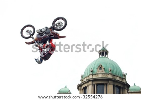 Motocross biker performing dangerous trick - back flip next to cupola of old stylish building isolated on white - stock photo