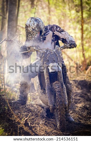 Motocross driver having a motor breakdown on wet and muddy terrain in Finland - stock photo