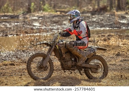 Motocross driver on muddy offroad track and wet terrain at cross country competition in Parola, Finland. - stock photo