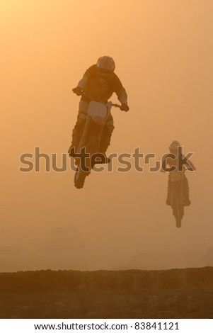 Motocross  jump in dusty - stock photo