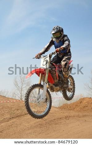 Motocross motorbike racer performs a jump - stock photo