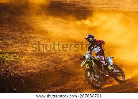 Motocross pilot in a turn during sunset with golden smoke on dirt track - stock photo