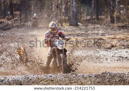 Motocross racer splashing mud on wet and muddy terrain in Finland. - stock photo