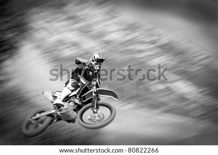 motocross rider in the air at high speed, black and white picture - stock photo