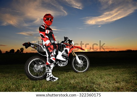 Motocross rider in the country side with sunset on background - stock photo