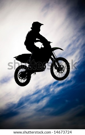 motocross rider making a jump in a dirt track race - stock photo