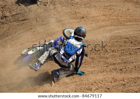 Motocross rider on the a motorbike falls - stock photo