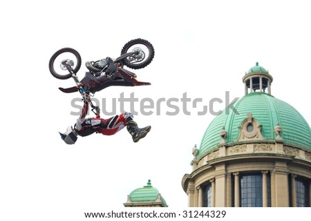 Motocross rider performing back flip over cupola of old building isolated on white. - stock photo