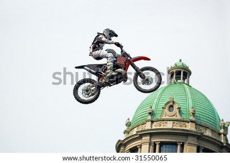 Motocross rider performing extreme jump next to cupola of old stylish building - stock photo