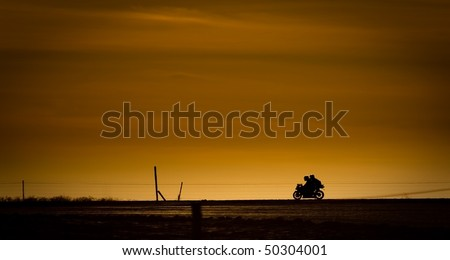 Motor bike in on a road in the sunset - stock photo