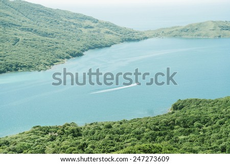 Motor boat sails on the sea in the bay, top view - stock photo