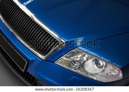 motor-car headlight and grate of radiator on a dark blue car - stock photo