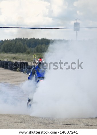 motor-cyclist on the start line into the smoke cloud - stock photo