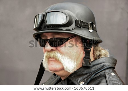 Motor cyclist with a military-style crash helmet and sunglasses.