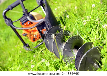 Motor earth auger on the grass - stock photo