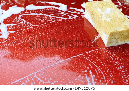Motor hood being cleaned with sponge and soap - stock photo