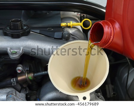 Motor oil from a red jug is being added with a funnel from the right side of a car. Yellow dipstick and cap are nearby. - stock photo