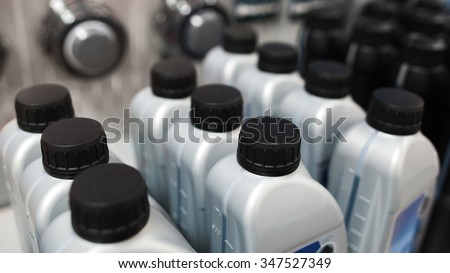 Motor oil in plastic bottles. Showcases of the tools store (shop) - stock photo