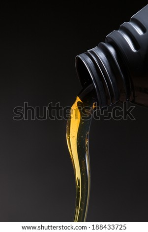 Motor oil pouring over black background - stock photo