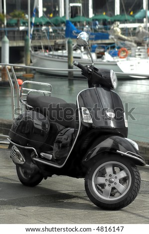 Motor scooter by the water - stock photo