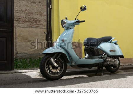 motor scooter parked in front of a building wall - stock photo