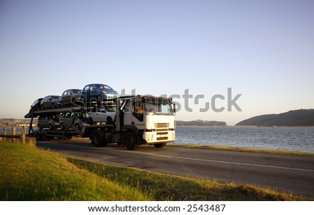 Motor vehicle carrier travelling in the countryside - stock photo